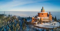 Aerial view of San Luca Sanctuary covered with snow in winter time with blue sky. Bologna, Italy.