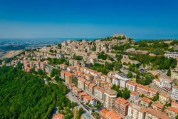 Aerial view of San Marino old town with old buildings and red roofs on the hill on a sunny day with clear sky. Picture from above with Italy behind in horizon