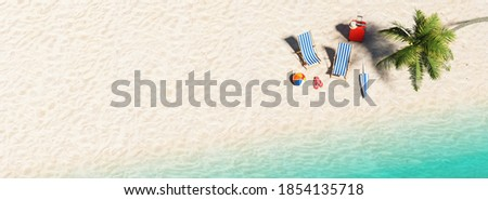 Aerial view of sandy beach and ocean and beach chair with beach ball flip-flop sandals, umbrella and suit case under a palm tree at the beach during a summer vacation in the Caribbean, with copy space