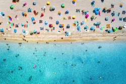 Aerial view of sandy beach with colorful umbrellas, swimming people in sea bay with transparent blue water at sunny day in summer. Travel in Mallorca, Balearic islands, Spain. Top view. Seascape