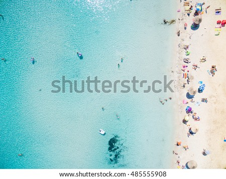 Aerial view of sandy beach with tourists swimming in beautiful clear sea water #485555908
