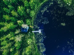Aerial view of Sauna house by the lake shore. Green forest and blue lake in Finland. Wooden pier with fishing boat.
