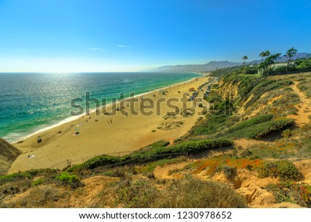 Aerial view of scenic Point Dume State Beach from Point Dume promontory on Malibu coast, Pacific Ocean in CA, United States. California West Coast. Blue sky, summer sunny day. Copy space.