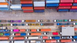 Aerial view of semi truck and trailer loading at logistic center, Business freight shipping import export transportation by semi truck trailer vehicle.
