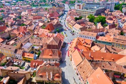 Aerial view of Sibiu traditional houses with brown-orange roofs and a street in the middle, near the city pedestrian area/center. View from the watch tower of Lutheran Cathedral of Saint Mary.