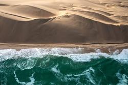 Aerial view of Skeleton coast sand dunes meeting the waves of Atlanic ocean. Skeleton coast, Namibia.