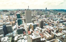Aerial view of skyscrapers cityscape in business district of Johannesburg - Architecture concept with modern building skyline in South Africa big city - Landscape on desaturated dramatic filtered look