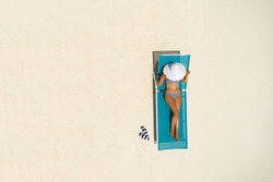 Aerial view of slim woman sunbathing lying on a beach chair in Maldives. Summer seascape with girl. Top view from drone.