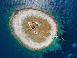 Aerial view of small island with lighthouse in Adriatic sea near Hvar island, Croatia made with drone. Top view. Summer vacation destination