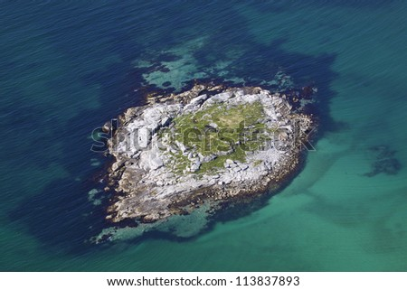 Aerial view of small rocky island in turquoise sea near norwegian coast