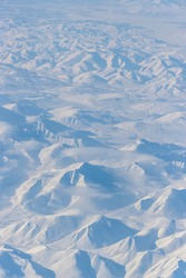 Aerial view of snow-capped mountains and clouds. Winter snowy mountain landscape. Travel to the far north of Russia. Korbendya Range, Kolyma Mountains, Magadan Region, Siberia, Russian Far East.