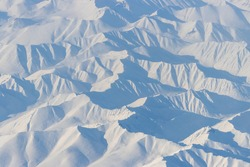 Aerial view of snow-capped mountains. Winter snowy mountain landscape. Travel to the far north of Russia. Nayakhan ridge, Kolyma Mountains, Magadan Region, Siberia, Russian Far East. Great background.