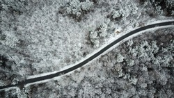 Aerial view of snow covered road in winter forest.