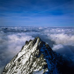 Aerial view of snow covered summit of Rysy mount with a sea of white fluffy clouds.Famous attraction Tatra mountains.Greatness of nature-Image