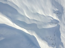 Aerial view of snow covered terrain in mountain area. Mountains in central Switzerland. Alps with snow in beautiful light with shadow and sun.
