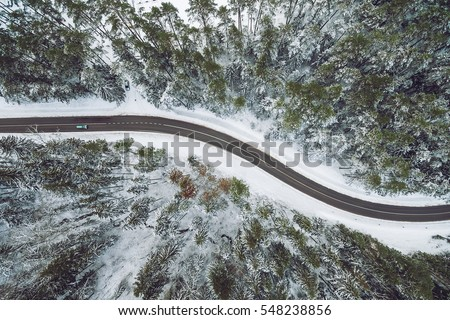 Aerial view of snowy forest with a road. Captured from above with a drone  #548238856