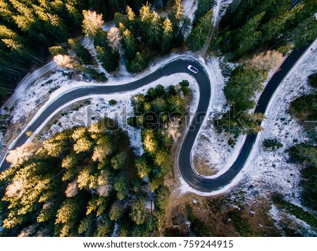 Aerial view of snowy forest with a road. Captured from above with a drone. Dolomites - Italy