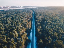 Aerial view of snowy road and forest. Winter season in Kaunas county, Lithuania
