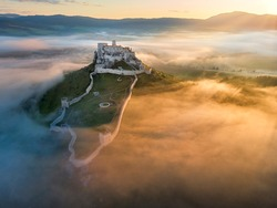 Aerial view of Spiš Castle, surrounded by fog, lit by morning sun. Extensive castle ruins above the valley against mountains in background. Magic colors, orange colored mist and blue shadows. Slovakia