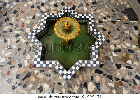 Aerial view of star shaped mosaic water fountain in courtyard in Fez, Morocco.