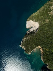 Aerial view of steep stone cliffs with green forest above transparent emerald water of Adriatic sea. Stones on seabed. Unspoiled nature of Montenegro coast. Budva. Scenic landscape. Balkans nature.