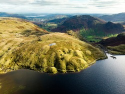 Aerial view of Stickle Tarn lake, located in the Lake District, Cumbria, UK. Popular tourist attractions in Great Langdale valley, famous for its glacial ribbon lakes and rugged mountains.