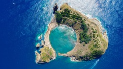 Aerial view of submerged volcano crater in the deep blue and azure Atlantic Ocean called Ilheu de Vila Franco do Campo which is part of the Azores on Sao Miguel Island, Portugal.