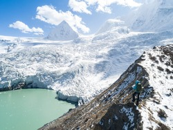 Aerial view of successful woman backpacker hiking up hill  in winter  high altitude mountains