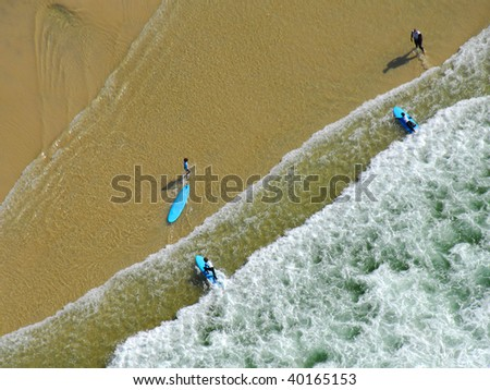 Aerial view of surfers at the water's edge
