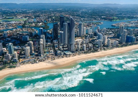Aerial view of Surfers Paradise on the Gold Coast with skyscrapers and waves crashing onto the golden beach