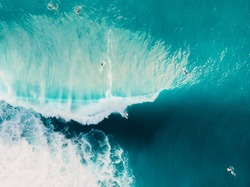 Aerial view of surfing at barrel waves. Blue waves in ocean and surfers