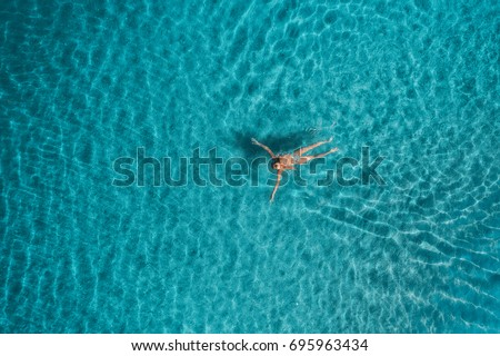 Aerial view of swimming woman in Blue Lagoon. Mediterranean sea in Oludeniz, Turkey. Summer seascape with girl, clear azure water, waves at sunrise. Transparent water.Top view from flying drone.Travel #695963434