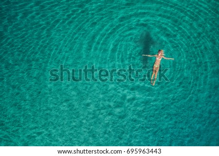 Aerial view of swimming woman in Blue Lagoon. Mediterranean sea in Oludeniz, Turkey. Summer seascape with girl, clear azure water, waves in sunny day. Transparent water. Top view from flying drone #695963443