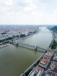 Aerial view of Széchenyi Chain Bridge over Danube river near Parliament palace, Budapest city, Hungary. Cars drive on road, boats float on river, ships moored near riverside. Historic centre, rooftop