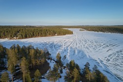 Aerial view of taiga forests of pine trees, white frozen lakes during the day. Beautiful winter landscape of northern terrain with drone.