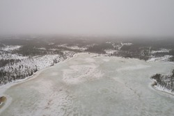 Aerial view of taiga forests of pine trees, white frozen lakes during the fog. Winter landscape of northern terrain with drone.