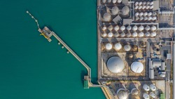 Aerial view of tank farm oil and gas terminal with lots of fuel petroleum chemical natural gas storage tank and petrochemical in the harbour, Business power and energy industrial tank storage .