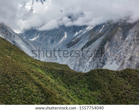 Aerial view of temperate rain forest some distance from steep eroding valley under clouds that obscure snowy mountain (upper left) in the Southern Alps of New Zealand, for motif of spectacle in nature #1557754040