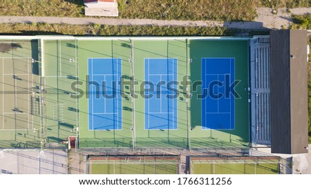 Aerial view of tennis court. Audience stand, football field on the side and other tennis field can be seen. Tennis players are training.