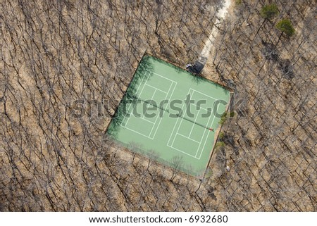 Aerial view of tennis court in bare wooded area.