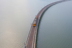 Aerial view of Thai local train on railway bridge at Pa Sak Jolasid Dam, the biggest reservoir in central Thailand, in Lopburi province with sea shore in transportation and travel concept.