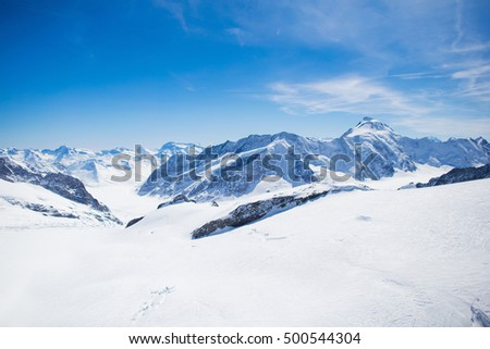 Aerial view of the Alps mountains in Switzerland. View from helicopter in Swiss Alps. Mountain tops in snow. Breathtaking view of Jungfraujoch and the UNESCO World Heritage - the Aletsch Glacier #500544304