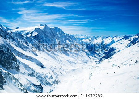 Aerial view of the Alps mountains in Switzerland. View from helicopter in Swiss Alps. Mountain tops in snow. Breathtaking view of Jungfraujoch and the UNESCO World Heritage - the Aletsch Glacier #511672282