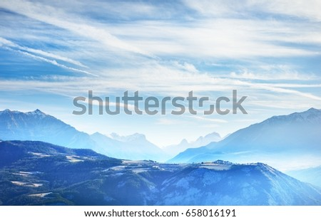 Aerial view of the Alps mountaintops and a mountain village near lake lac de Serre-Poncon on a clear sunny day, France