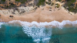 Aerial view of the beach of Los Castillejos with sand and blue sea with transparent water. Top view, amazing natural beach background. Atlantic Ocean in Caños de Meca, Cádiz, Andalusia, Spain.