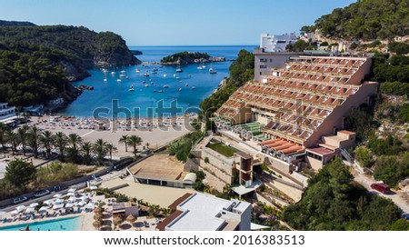 Aerial view of the beach of Port Sant Miquel on the north shore of Ibiza island in Spain - Isolated bay sided with large hillside hotels in the Balearic Islands Photo stock ©