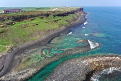 Aerial view of the beautiful Double-Heart of Stacked Stones or Twin-Heart Fish Trap, which is an old traditional fishing weir by the coastal cliffs of a cape, in Cimei Isalnd, Penghu, Taiwan