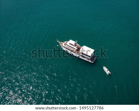 Aerial view of the big motor vessel with lifeboat, white sides and wooden deck; boats  concept. #1495127786