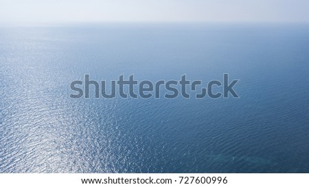 Aerial view of the blue ocean surface of the Atlantic Ocean. The sun, above the horizon, reflects its sunlight on the sea.