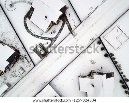 Aerial view of the buildingss roofs covered with  snow in a small town